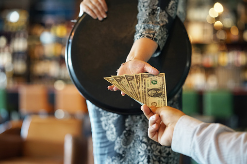 The hand of a restaurant waitress takes $4 in cash for a tip from a customer.
